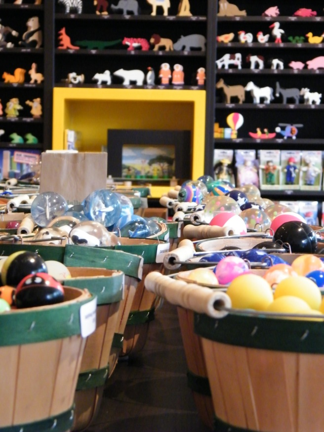 Wooden baskets with dowel handles full of small toys. In the background, a shelved wall full of wooden animal shapes.