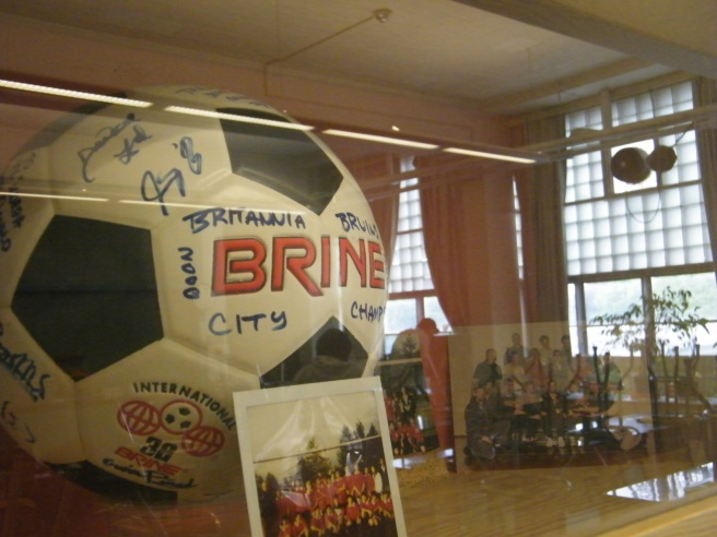 A glassed-in shelf, holding a signed soccer ball with photos and memorabilia. The reflection of a classroom can be seen in the glass, especially the large, paned windows.
