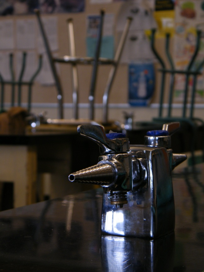 A table in a science classroom, with a gas nozzle in the foreground, stools stacked on desks in the background.