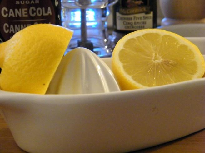 A split lemon resting in the juicer.
