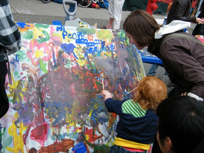 Kids collaboratively paint a picture, where cars usually are.