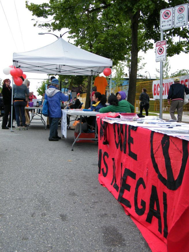 Community groups set up along the street, including No One is Illegal.