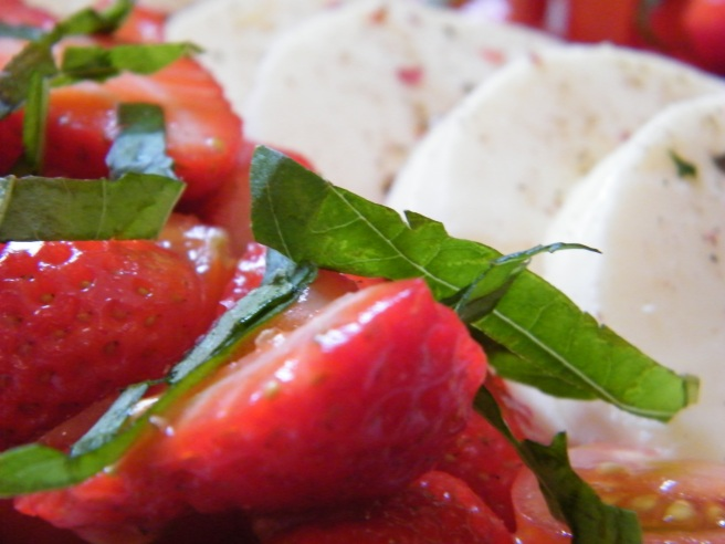 Close up of the salad, focusing on a piece of basil atop sliced strawberries and cherry tomatoes. The slices of mozzarella are in the background.
