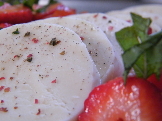This shot emphasizes the sliced mozzarella, drizzled with olive oil and with crushed peppercorns scatterd across them.