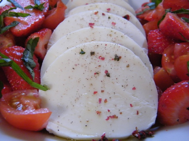 The sliced mozzarella, drizzled with oil and sprinkled with crushed pink peppercorns. Flanked on either side by mixed, sliced strawberries and tomatoes, garnished with shredded basil.
