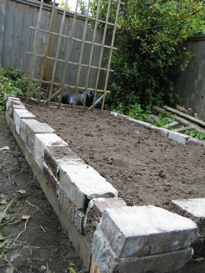 A raised garden bed made with bricks laid on top of two-by-fours, with a wooden trellis on one end.