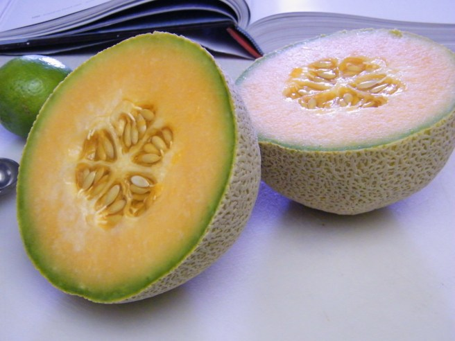 Sliced cantaloupe, with a cookbook, a lime and a measuring spoon visible in the background.
