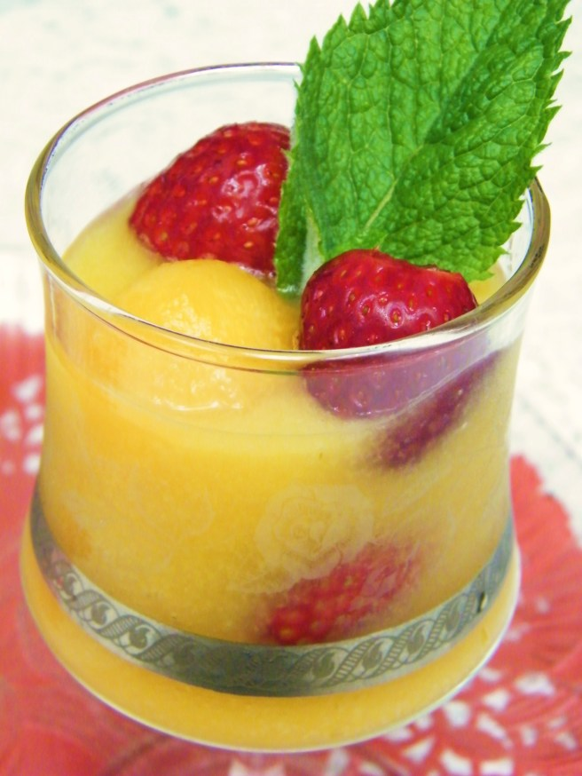 An etched wine glass full of melon soup, with melon balls and strawberries and a sprig of mint. Everything sits on a tray atop a red doily on a white lace tablecloth.
