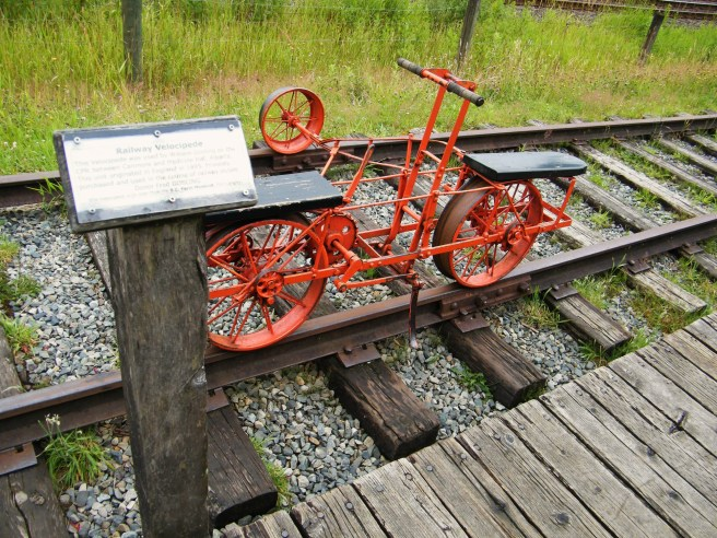 An orange velocipede, which was used for railway inspections, atop the rail.