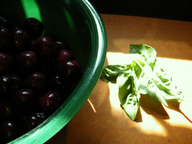 A dark green bowl full of cherries, atop a brown cutting board with a small pile of basil sitting in a patch of sun.