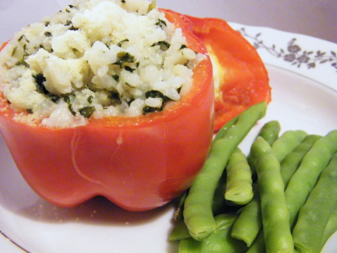 A red pepper stuffed with the rice, accompanied by green beans.