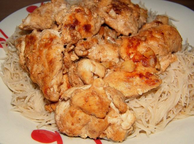 Chicken atop brown rice vermicelli.