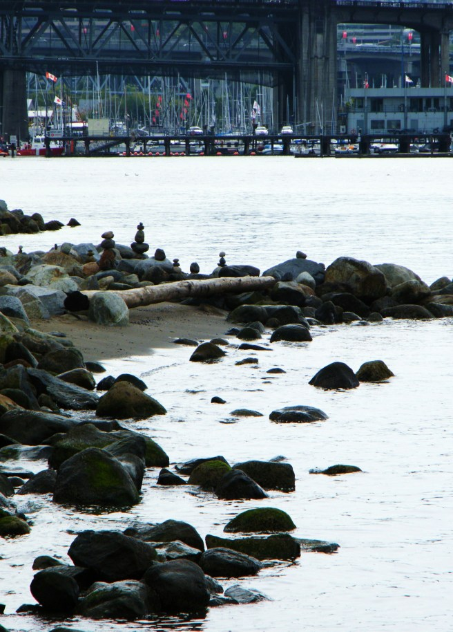 Rocks along the ocean, with a marina and a bridge across the water.