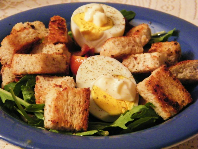 The finished salad, with greens on the bottom and bacon, croutons and mayonnaise-dolloped eggs on top.