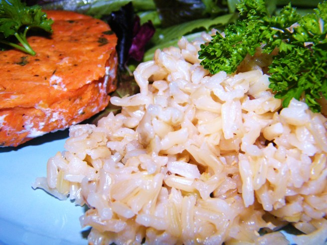 Cardamom Rice Pilaf, decorated with parsley, with a salmon cake and green salad.