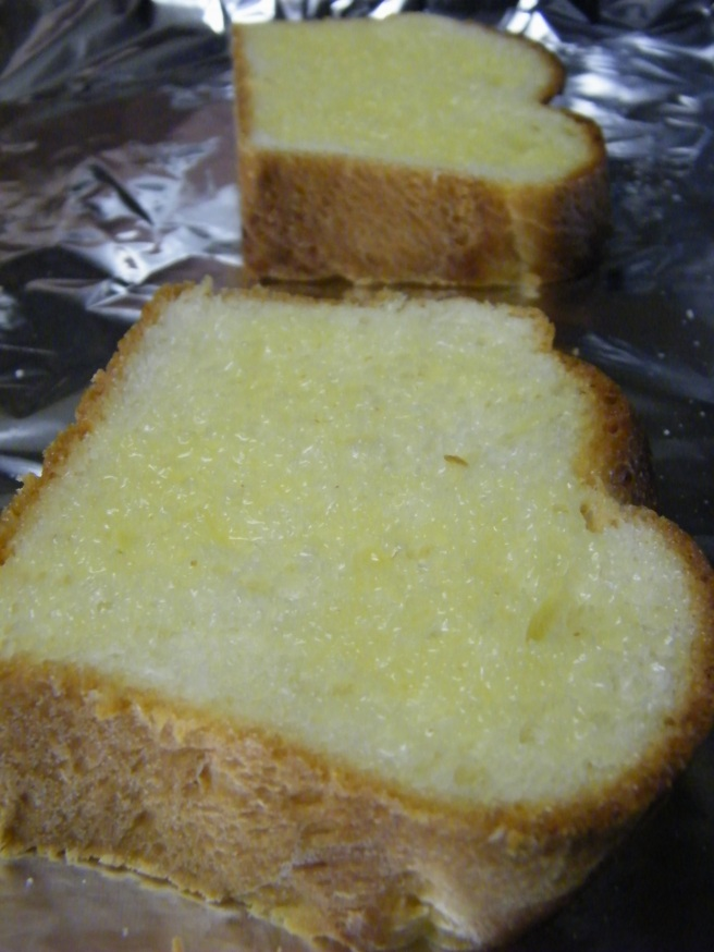 Slices of brioche, brushed with melted butter, ready to slide into the oven.