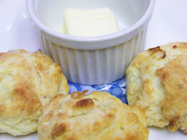 Three biscuits on a white and blue plate, with a bit of butter in a ramekin.