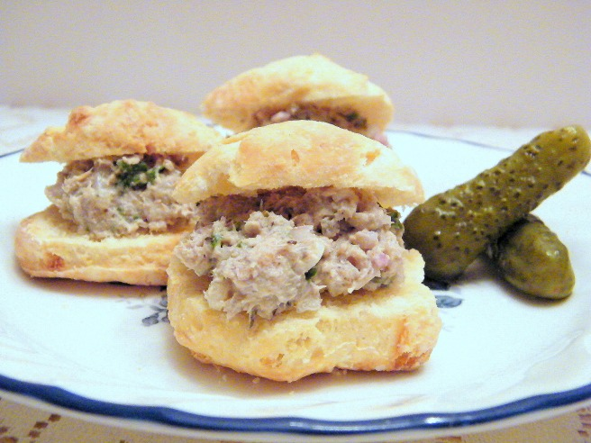 A plate full of rillettes-stuffed biscuits, with cornichons on the side.