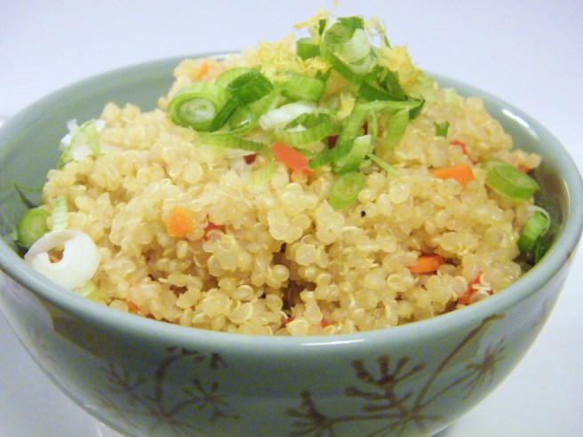 A bowl of quinoa pilaf, dressed with green onion and lemon zest.