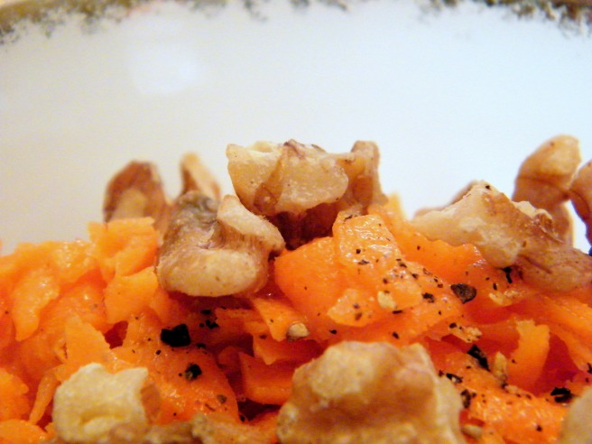 A close up of the carrot salad, dressed with toasted walnuts.