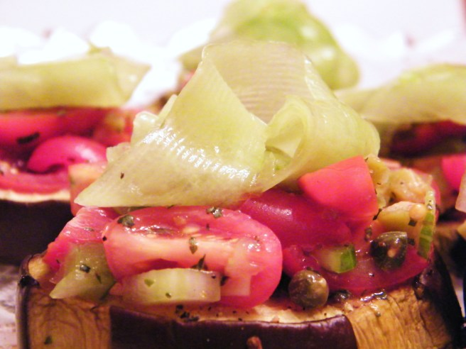 Roasted slice of eggplant, loaded with tomato salad and topped with ribbons of cucumber.