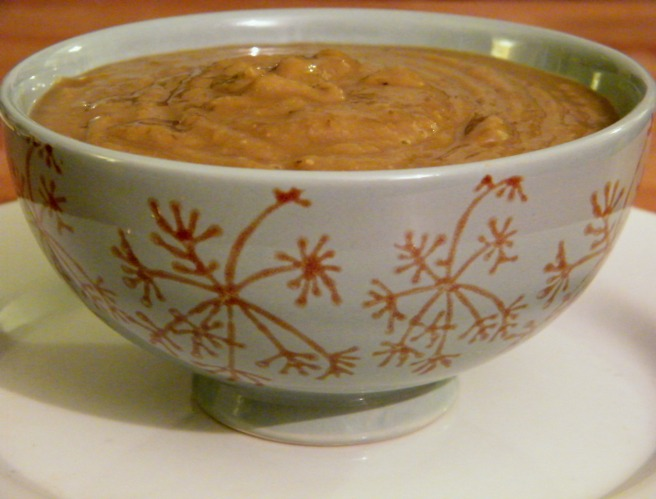 Lentil Soup in a blue bowl with a dill seed pattern, on a white plate atop a wooden table