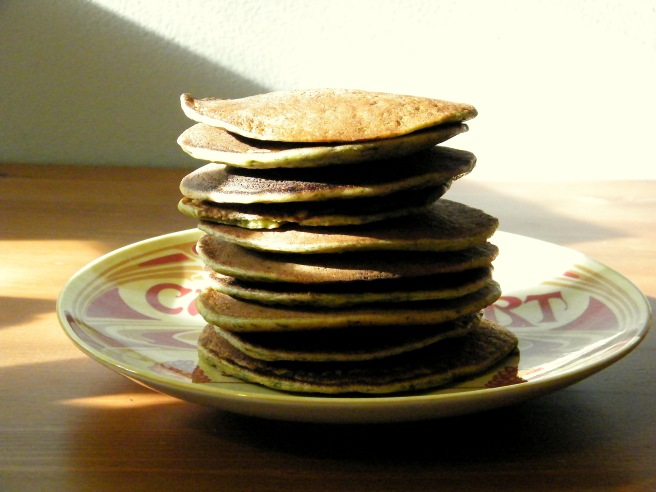 A stack of Swiss chard pancakes on a yellow and red plate that says Camembert, atop a wooden table with light and shadows cutting across the frame.