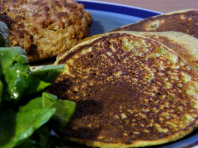Swiss chard pancakes with lamb burgers and spinach salad, on a blue plate with a darker blue stripe around the edge.