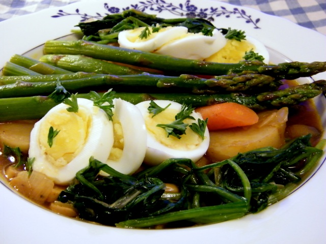 Spinach, asparagus, carrots, potatoes, and slices of hard boiled eggs arranged over a bowl of broth.